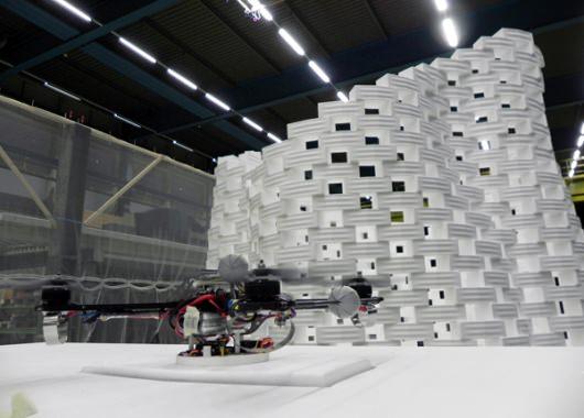 Unos de cuadracópteros con la estructura al fondo